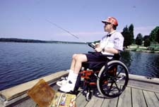 man in wheelchair fishing on accessible dock